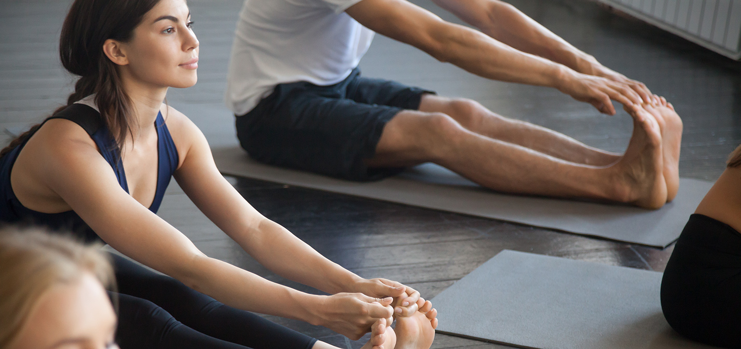 Group of young sporty people practicing yoga lesson with instructor concept, sitting in paschimottanasana exercise, Seated forward bend pose, friends working out in club, indoor full length, studio